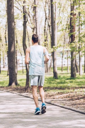 Photo for Back view of young man in sportswear jogging along walkway in park - Royalty Free Image
