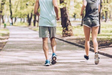 Photo pour Coup recadré de l'homme dans le jogging de femme ensemble le long de la passerelle dans le stationnement - image libre de droit