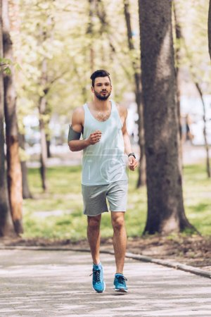 Photo for Handsome man in sportswear running along pavement in green park - Royalty Free Image