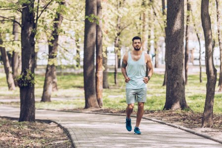 Photo for Handsome sportsman jogging along walkway in green sunny park - Royalty Free Image