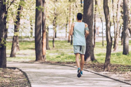 Photo for Back view of young sportsman jogging along walkway in park - Royalty Free Image
