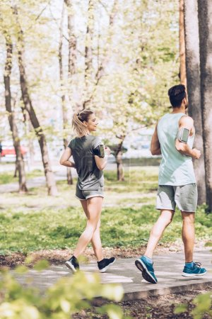 selective focus of young sportswoman and sportsman running together in park