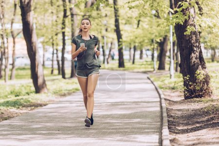 Photo for Attractive young woman holding smartphone and listening music in earphones while jogging in park - Royalty Free Image