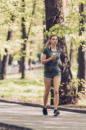 Photo for Pretty young sportsman running and park, holding smartphone and listening music in earphones - Royalty Free Image