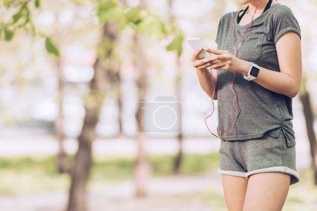Photo pour Coup recadré de sportive dans le tracker de remise en forme utilisant le smartphone et la musique d'écoute dans des écouteurs - image libre de droit