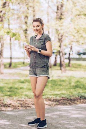 Photo pour Sportive attirante souriant à l'appareil-photo tout en retenant le smartphone et écoutant la musique dans des écouteurs - image libre de droit