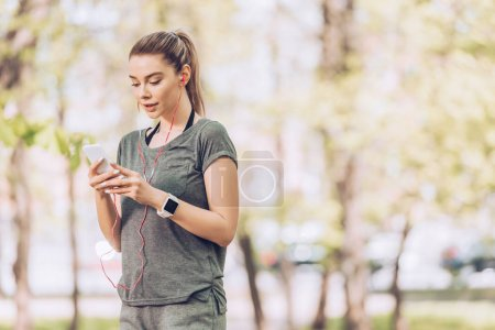 Photo for Beautiful sportswoman holding smartphone and listening music in earphones - Royalty Free Image