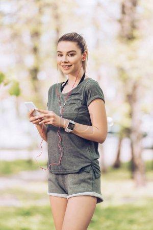 Photo pour Femme attrayante en vêtements de sport en utilisant un smartphone et écouter de la musique dans les écouteurs tout en souriant à la caméra - image libre de droit