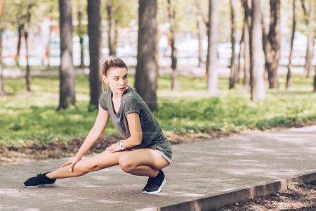 Photo pour Attrayant jeune femme en vêtements de sport regardant loin tout en exerçant dans le parc ensoleillé - image libre de droit