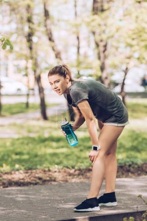 Photo for Tired thirsty sportswoman looking away while holding sport bottle - Royalty Free Image