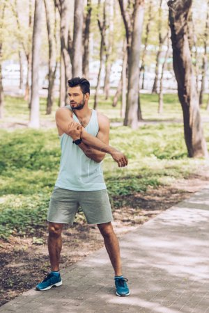 Photo for Handsome young man in sportswear and sneakers training in park - Royalty Free Image