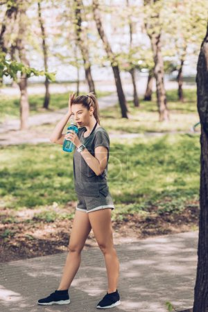 Photo for Attractive young woman in sportswear drinking from sport bottle in park - Royalty Free Image