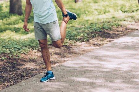 Photo pour Coup recadré de l'homme dans des vêtements de sport et des baskets s'étirant dans le stationnement - image libre de droit