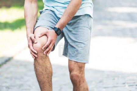 Photo pour Vue partielle du sportif dans le traqueur de forme physique touchant le genou blessé - image libre de droit