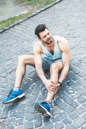 Foto de Young sportsman touching injured leg while sitting on pavement and suffering from pain - Imagen libre de derechos