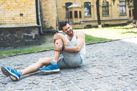 Photo pour Beau sportif criant tout en s'asseyant sur le trottoir et touchant la jambe blessée - image libre de droit
