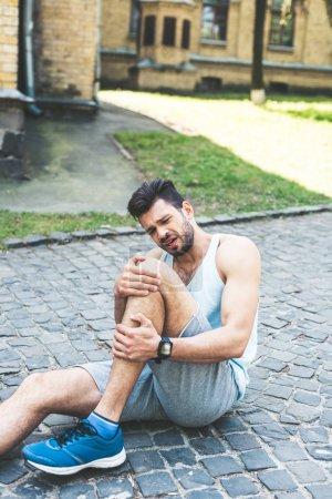 Photo pour Un jeune sportif souffrant de douleur alors qu'il est assis sur la passerelle et qu'il touche une jambe blessée - image libre de droit