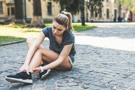 Photo pour Young pretty sportswoman sitting on pavement and touching injured leg - image libre de droit