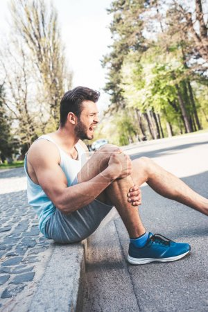 Foto de Young sportsman suffering from pain while sitting on pavement border and touching injured leg - Imagen libre de derechos