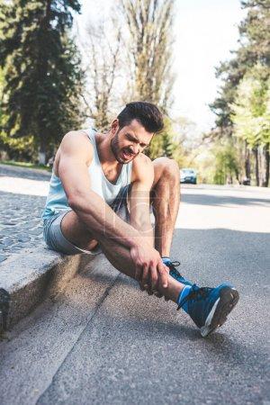 Foto de Handsome sportsman touching injured leg while sitting on border and suffering from pain - Imagen libre de derechos
