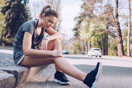 Photo pour Kiev, Ukraine - 25 avril 2019: Une jeune sportive souffrant de douleurs alors qu'elle était assise sur la chaussée et touchait une jambe blessée. - image libre de droit