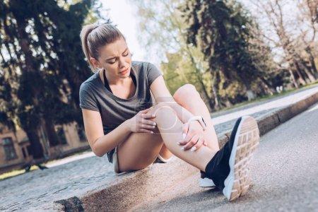 Foto de Mujer deportiva triste que sufre de dolor mientras se sienta en el pavimento y toca la pierna lesionada - Imagen libre de derechos