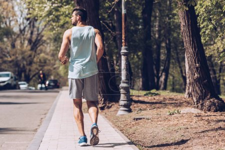 Photo for Back view of young sportsman running along pavement near roadway - Royalty Free Image