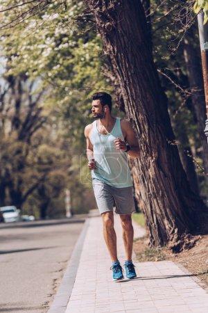 Photo pour Beau sportif écoutant de la musique dans des écouteurs tout en faisant du jogging seul trottoir près de la chaussée - image libre de droit