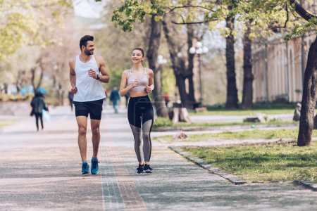 Photo for Young sportsman and sportswoman smiling while jogging along park alley - Royalty Free Image