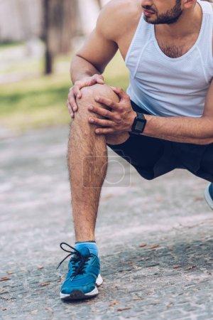 Photo pour Coup recadré de l'homme dans sportswear toucher le genou blessé - image libre de droit