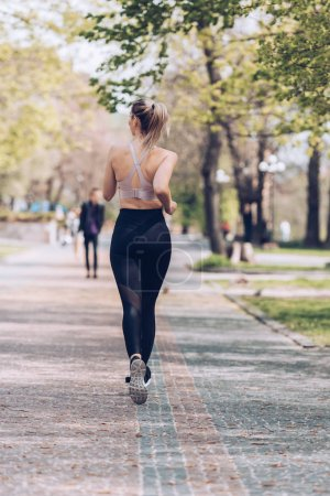 Photo for Back view of young sportswoman jogging along wide walkway in park - Royalty Free Image