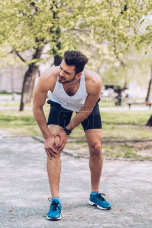 Photo for Handsome sportsman suffering from hurt while touching injured knee - Royalty Free Image