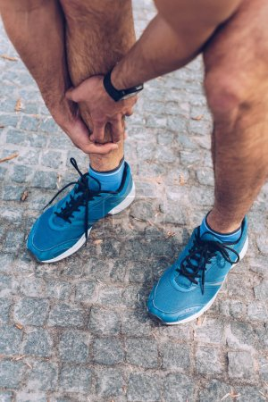 Photo for Cropped shot of sportsman in sneakers touching injured leg - Royalty Free Image