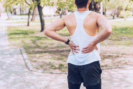 Foto de Vista trasera de joven deportista de pie en el parque y tocar la espalda lesionada - Imagen libre de derechos