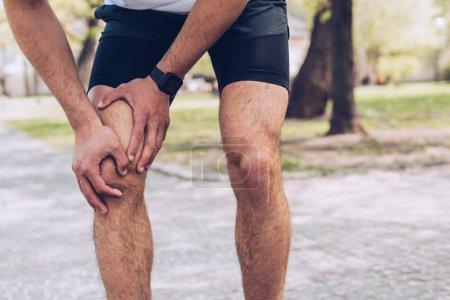 Photo pour Coup de feu recadré du jeune sportif debout dans le parc et touchant le genou blessé - image libre de droit