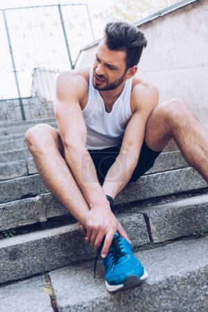 Photo for Upset sportsman sitting on stairs and suffering from pain while touching injured knee - Royalty Free Image