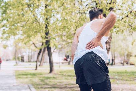 Foto de Back view of sportsman suffering from pain while touching injured back - Imagen libre de derechos