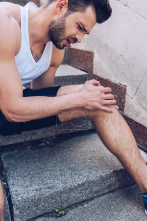 Foto de Young sportsman touching injured knee while sitting on stairs and suffering from pain - Imagen libre de derechos