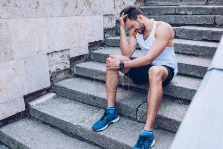 Foto de Deportista herido que sufre de dolor mientras se sienta en las escaleras y se sostiene de la mano cerca de la cabeza - Imagen libre de derechos
