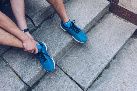 Photo for Cropped shot of man in sneakers sitting on stairs and touching injured leg - Royalty Free Image