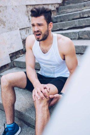 Foto de Enfoque selectivo de deportista lesionado gritando mientras se sienta en las escaleras y sufre de dolor - Imagen libre de derechos