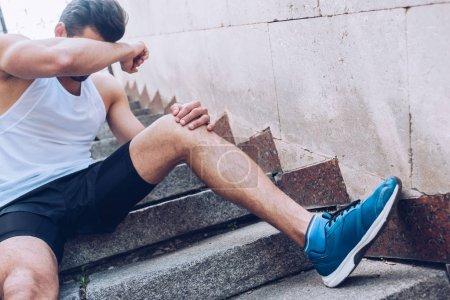 Foto de Deportista lesionado molesto que sufre de dolor mientras se sienta en las escaleras y cubrir la cara con la mano - Imagen libre de derechos
