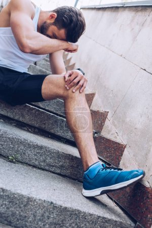 Photo for Injured sportsman suffering from pain while sitting on stairs and holding hand near face - Royalty Free Image