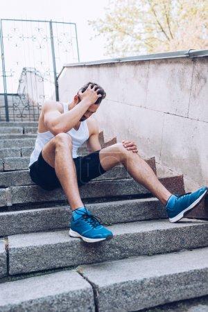 Foto de Deportista herido sentado en las escaleras y sufriendo de dolor mientras se sostiene de la mano en la cabeza - Imagen libre de derechos