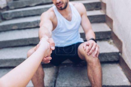 Photo pour Coup recadré de la femme donnant la main au sportif blessé s'asseyant sur des escaliers et souffrant de la douleur - image libre de droit