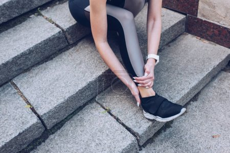 Foto de Cropped shot of sportswoman sitting on stairs and touching injured leg - Imagen libre de derechos
