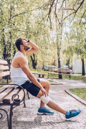 Foto de Deportista lesionado con vendaje elástico en la rodilla que sufre de dolor mientras se sienta en el banco en el parque - Imagen libre de derechos