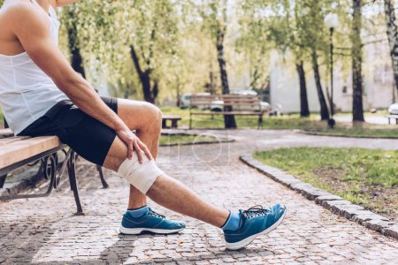 Photo for Partial view of injured sportsman sitting on bench and touching elastic bandage on knee - Royalty Free Image