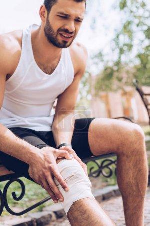 Photo for Upset sportsman sitting on bench and touching elastic bandage on injured knee - Royalty Free Image