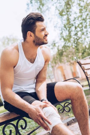 Photo for Injured sportsman looking away while sitting on bench and touching elastic bandage on knee - Royalty Free Image